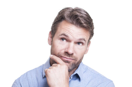 Portrait of young handsome bearded Caucasian man with hand on chin and eyes looking away as he thinks on white background