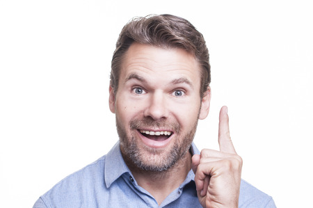 Portrait of handsome bearded Caucasian man holding up one finger and smiling because he has a bright idea on white background