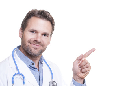 Handsome bearded male medical physician in white lab coat points finger toward upper right corner of frame on white background with copy space Stock Photo