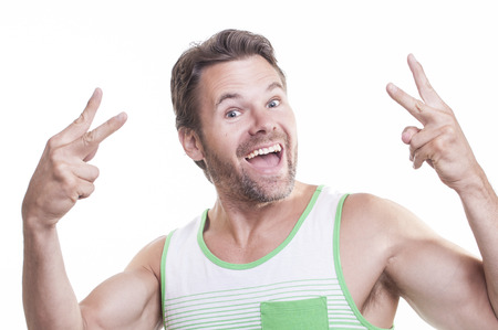 exalted: Crazy thrilled bearded muscular Caucasian man in tank top smiles crazy big and makes peace sign gesture with both hands on white background Stock Photo