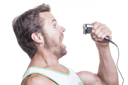 electric razor: Scruffy Caucasian man ferociously fights back electric razor from reaching his bearded face on white  background