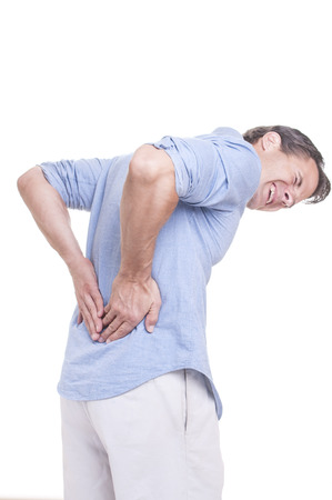 throb: Handsome young Caucasian man in blue shirt struggles with intense back pain on white background