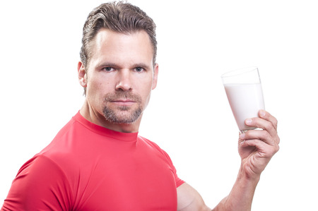 staunch: Portrait of handsome muscular Caucasian man with goatee wearing red athletic shirt holding glass of milk on white background