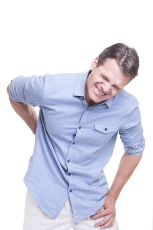 pain: Handsome young Caucasian man in blue shirt struggles with intense back pain on white background