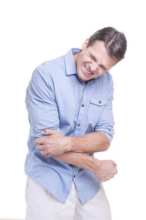 codo: Hombre caucásico hermoso joven de pie y vistiendo camisa azul sufre intenso dolor en el codo en el fondo blanco Foto de archivo