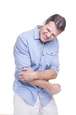 Young handsome Caucasian man standing and wearing blue shirt suffers intense elbow pain on white background