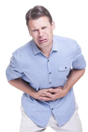 dolor de estomago: Hombre de raza caucásica en camisa azul llora en el dolor extremo mientras presiona las manos contra el dolor en el estómago en el fondo blanco