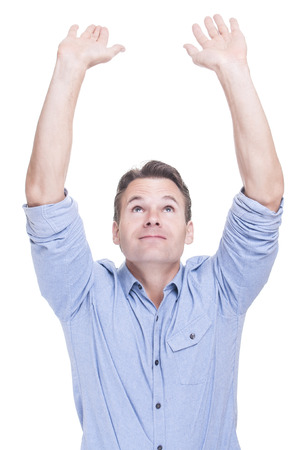 Handsome young Caucasian man in blue shirt holds both hands up in air on white background photo