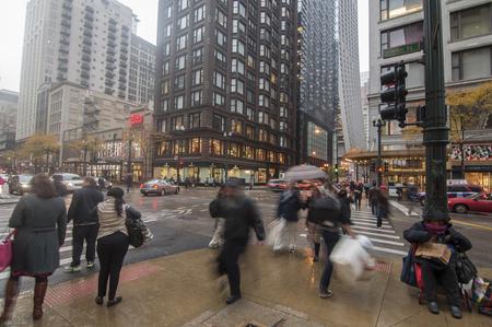 hustle: CHICAGO, USA - 30 Ottobre 2013: tutti i tipi di persone Hustle circa durante l'ora di punta serale in un giorno di autunno piovigginosa all'intersezione di Stato e di Madison a Chicago, Illinois, il 30 ottobre 2013