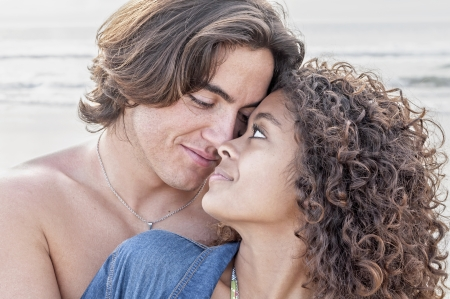 Young Caucasian man closely embraces young pretty Hispanic woman while gazing into each others eyes on beautiful beach Archivio Fotografico