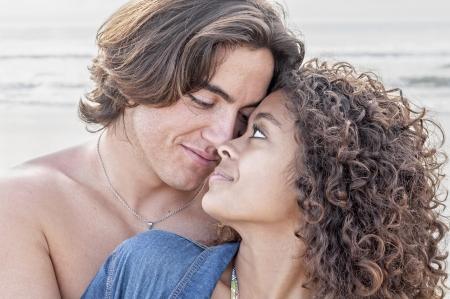 Jonge blanke man nauw omarmt jonge mooie Spaanse vrouw terwijl kijken in elkaars ogen op prachtige strand