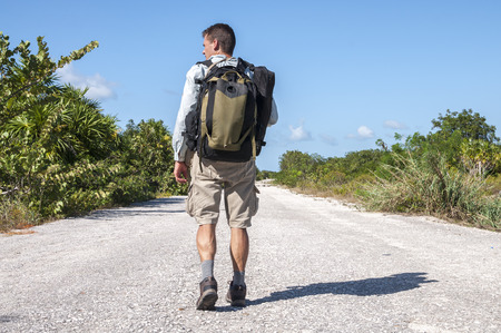 vagabond: Male hiker with backpack and gear walking alone down lonely asphalt road flanked by tropical vegetation