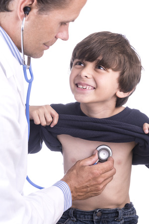 Young handsome Caucasian boy smiles at doctor in white lab coat photo