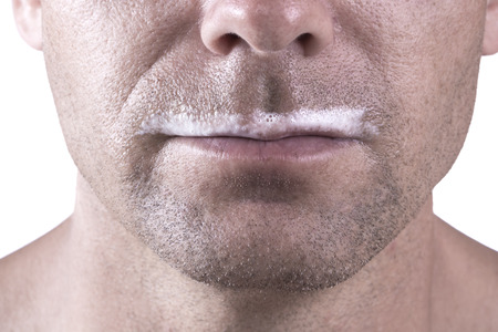 upper half: Macro closeup of lower half of mans face with thick white milk covering upper lip on white background