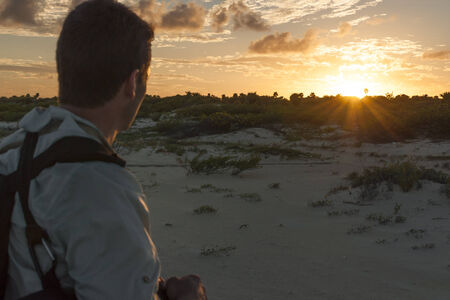 roo: Male hiker observes last rays of daylight as the sun sets over the tropical Yucatan peninsula near Cancun, Mexico