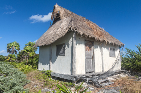 thatched house: Tiny one room palm thatched roof house in tropical surroundings near Cancun, Mexico Editorial