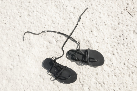 Black homemade sandles with leather straps on white sand beach