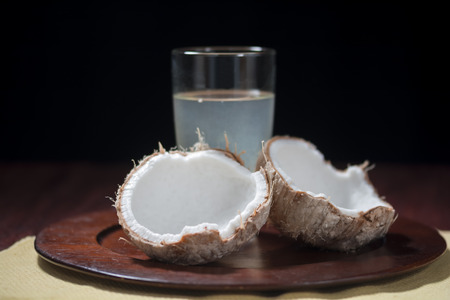 Fresh young coconut in broken shell with glass of coconut water on platter with black background photo