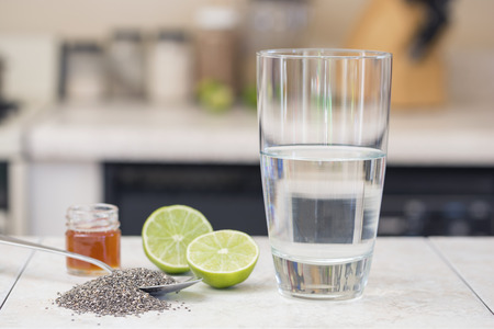 Chia seed, glass of water, honey, limes, ingredients used to make chia beverage called iskiate or chia fresca