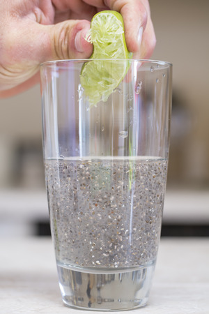 Hand squeezes lime extracting juice into glass of water and chia seed photo