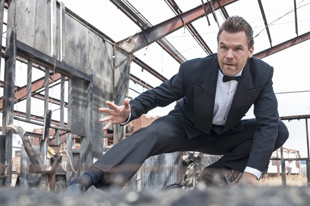 scene: Handsome tough Caucasian man in black tuxedo poses in action stunt scene in destroyed warehouse