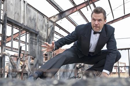 Hombre caucásico duro hermoso en smoking negro posa en escena de dobles de acción en el almacén destruido