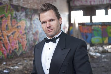 trashy: Well dressed handsome Caucasian man wearing tuxedo in trashy urban ghetto setting