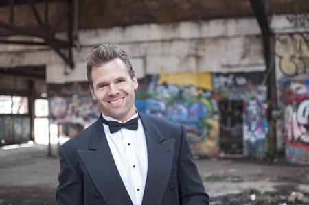 run down: Smiling handsome Caucasian man wearing black tuxedo in run down urban ghetto setting