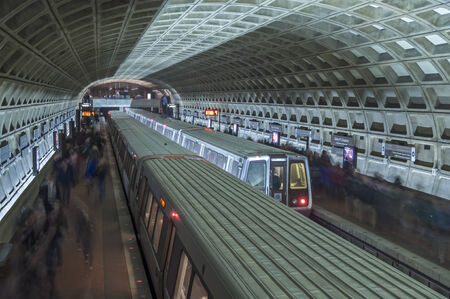 Two trains stop for passengers at metro stop in interesting architecturally designed underground tunnel at Union Station in Washington D C