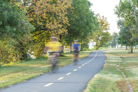 gravelly: Unrecognizable bicyclists ride on asphalt exercise pathway winding through Gravelly Point Park in Arlington, Virginia on autumn morning Stock Photo