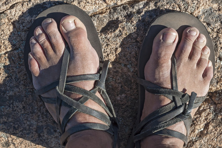 dirty feet: Top view of weathered feet of man wearing homemade rustic leather sandals standing on granite rock Stock Photo