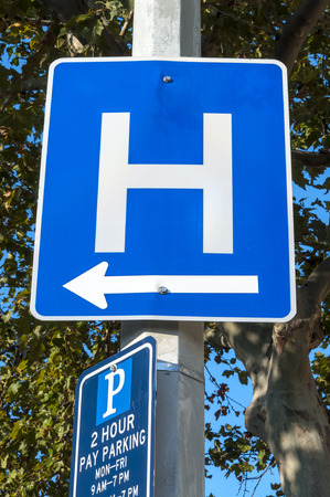 cement pole: Metal blue traffic sign with white letter H and arrow indicating direction to hospital