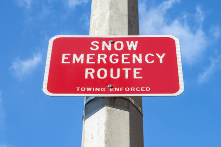 Metal red traffic sign indicating Snow Emergency Route attached to concrete post with blue sky background