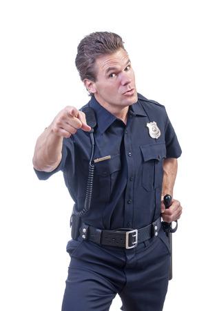 Männliche kaukasischen Polizist in blauer Uniform Polizist zeigt Finger anklagend in die Kamera beim Platzieren anderen Hand auf schwarzem Schlagstock auf weißem Hintergrund