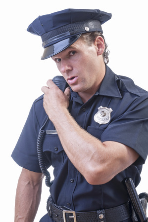Male Caucasian police officer in blue cop uniform talks on his radio receiver on white background Stock Photo