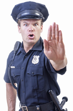 Male Caucasian police officer in blue cop uniform holds up hand in stop gesture on white background