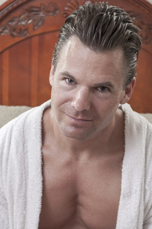 bath robe: Portrait of handsome muscular Caucasian man with dripping wet skin and hair wearing white bath robe in bedroom
