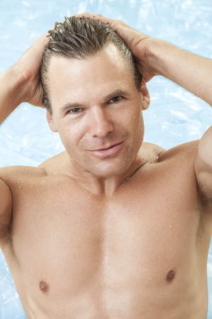 chest hair: Portrait of muscular sexy shirtless male swimmer getting out of water as he combs back hair with hands and smiles Stock Photo