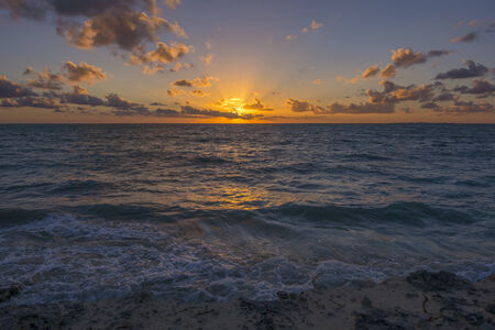 over the sea: Magnificent orange rays radiate from sun as it rises from behind the clouds over the Caribbean Sea at Isla Blanca near Cancun, Mexico Stock Photo