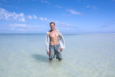 Sexy muscular sonriendo hombre de raza caucásica llevaba camisa desabrochada mientras disfruta de vacaciones en la playa poco profunda laguna tropical del mar Caribe Foto de archivo - 29431772