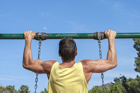 Back view of muscular man in yellow tank top performing pull up exercise on playground swing outdoors  photo