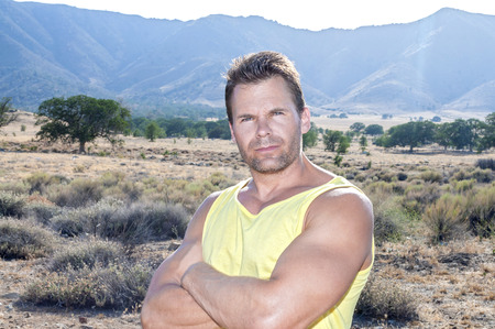 rugged: Tough looking muscular Caucasian man with arms crossed looks into camera while standing in natural outdoor countryside surroundings