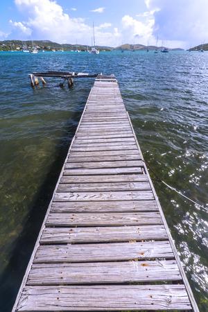 extends: Long plank wood dock extends into quiet bay of Ensenada Honda on the Caribbean island of Isla Culebra in Puerto Rico Stock Photo