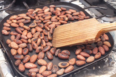 Wooden spoon stirring hot skillet on stove toasting whole cocoa beans