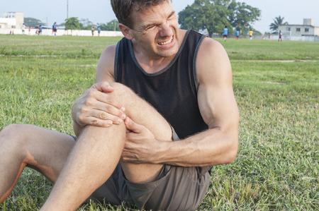 piernas hombre: El hombre sufre lesión muscular dolorosa y tiene zona dolorida con las manos mientras se sienta en el campo de juego de hierba
