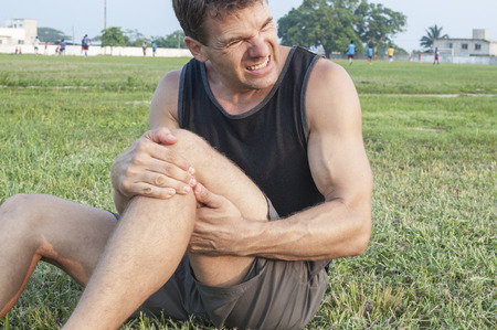 knees: Man suffers painful hamstring injury and holds painful area with hands as he sits on grassy ball field