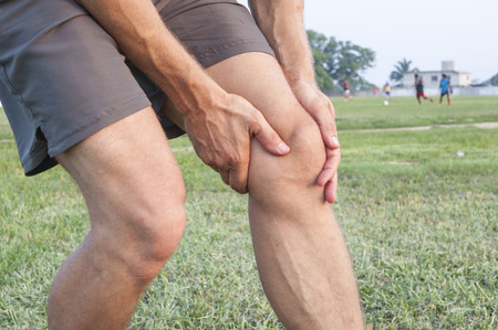 Closeup of athletic Caucasian man holding his painful knee on soccer field photo