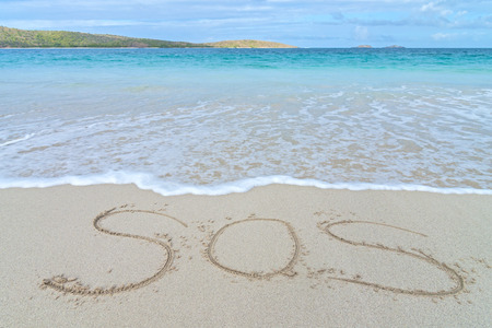 SOS nood teken geschreven in het zand van tropisch eiland strand boven water Stockfoto