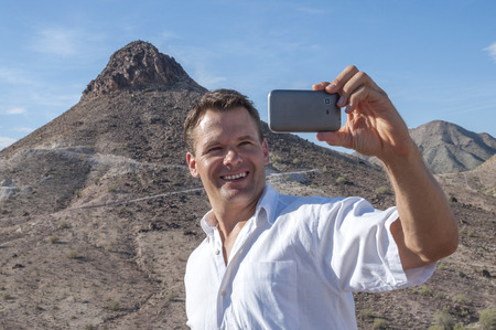 Handsome Caucasian man poses and smiles to take a self portrait in desert mountains photo