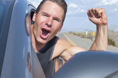 Close-up van de knappe vrije blanke man rijden auto met hoofd uit raam naar beneden woestijnweg als hij lacht met extreme opwinding en golven arm